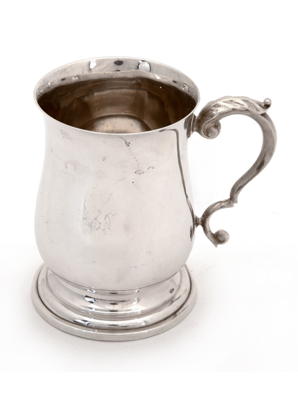 plain baluster shaped silver half pint christening mug with a scroll and leaf handle