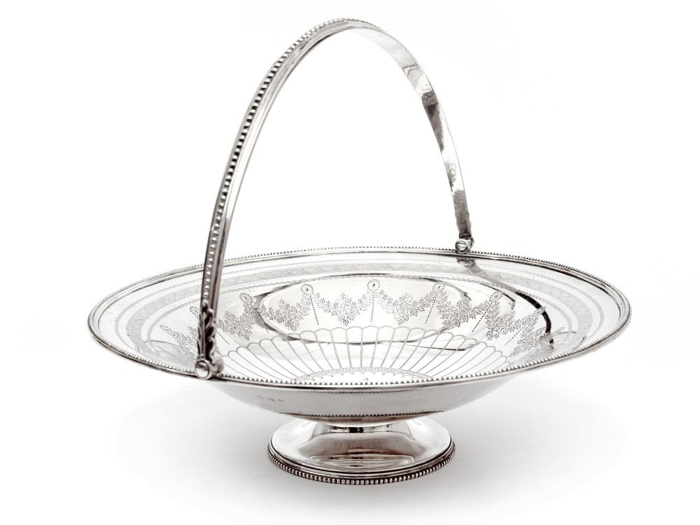 antique silver plated circular basket with a beaded border and swing handle