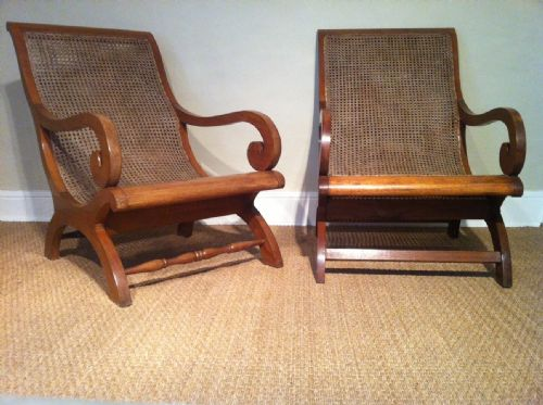 a matched pair of colonial teak and caned plantation chairs c 1920