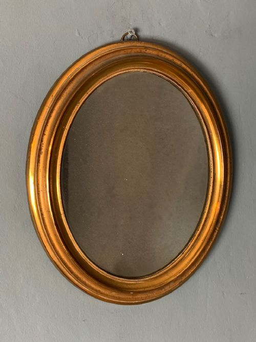 a small mid 19th c gilt brass oval mirror with original sparkly plate