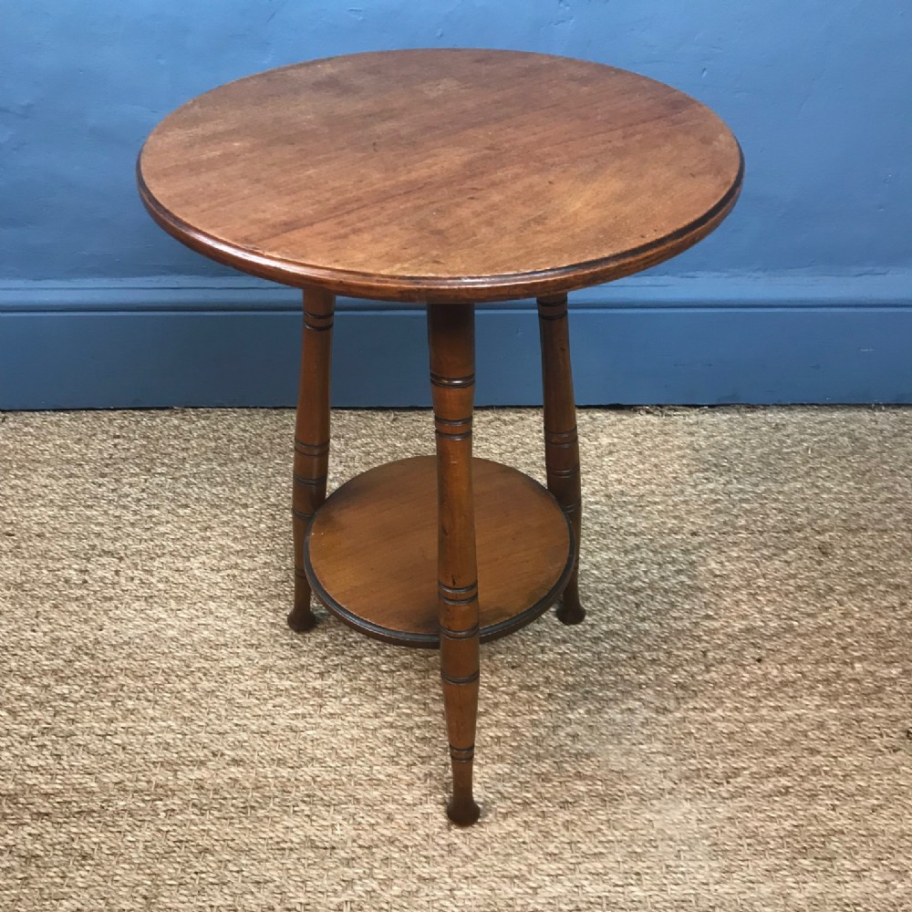 an aesthetic movement walnut circular 2 tier table circa 1880 in the style of e w godwin