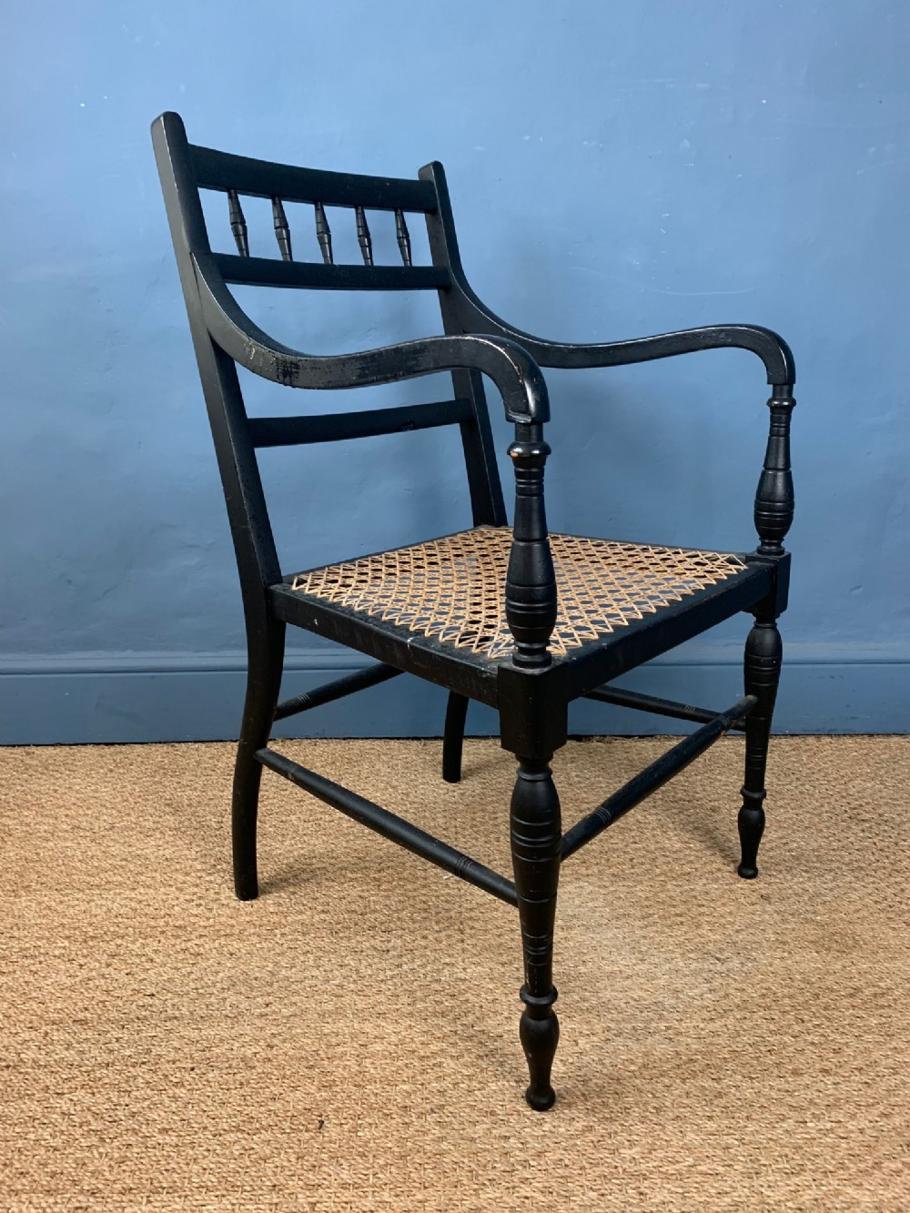 an aesthetic movement ebonised and caned arm chair circa 1890