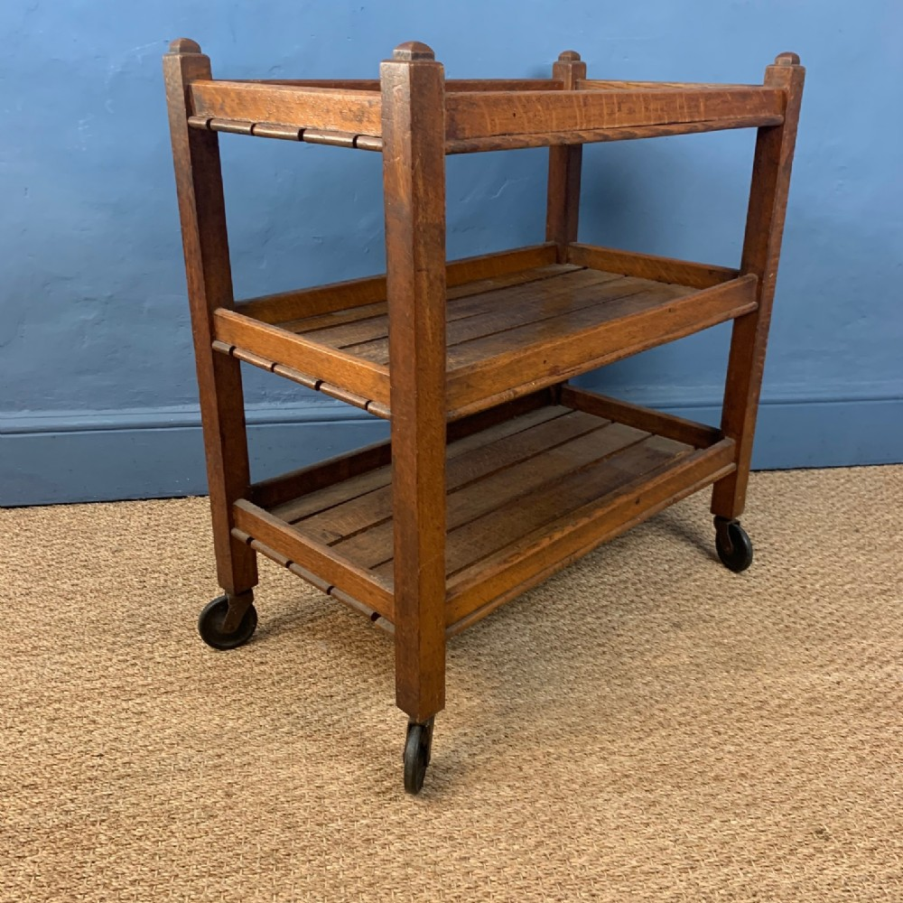 a 1920's oak trolley with slatted shelves on three tiers