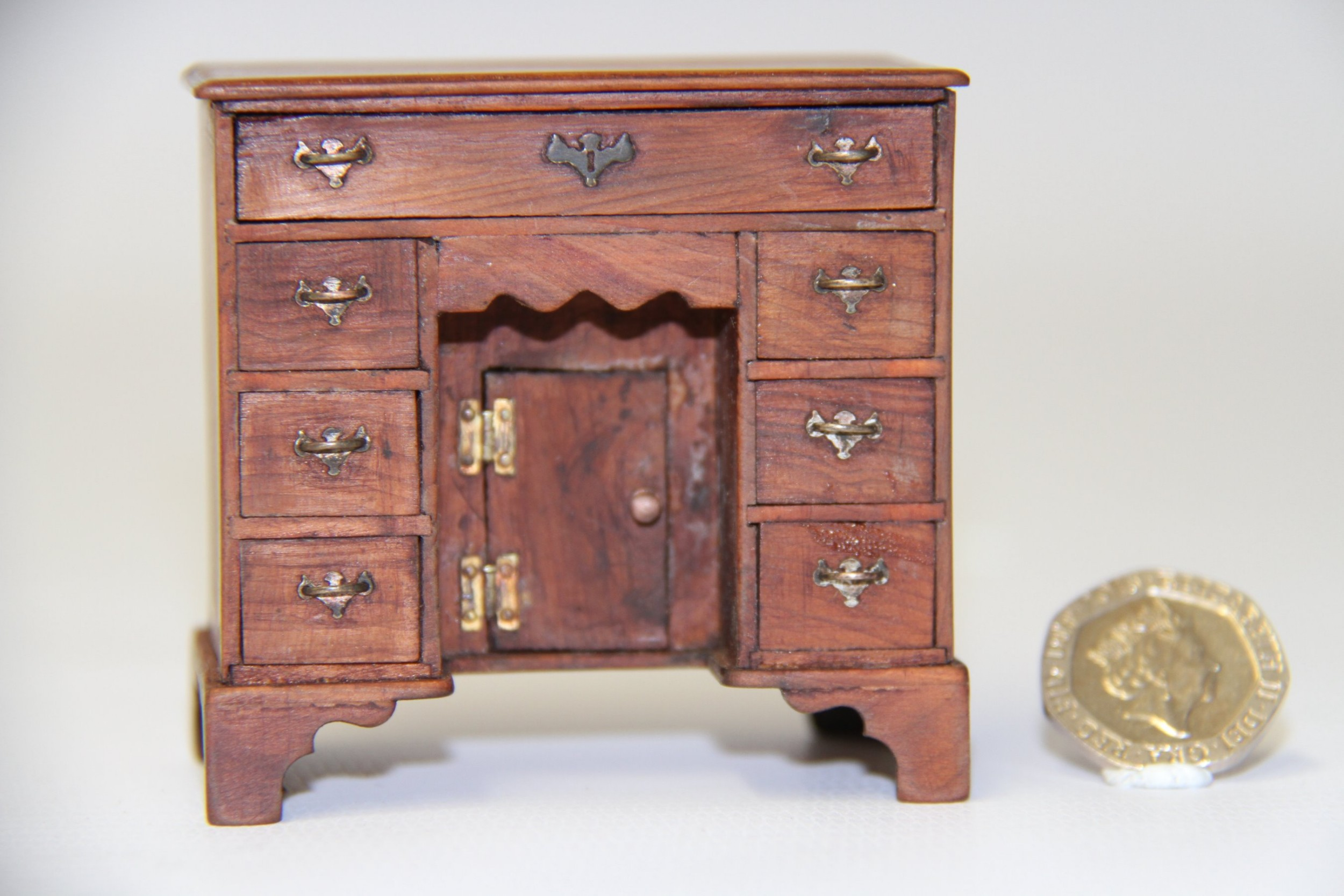 a miniature small scale model of a yew wood kneehole desk