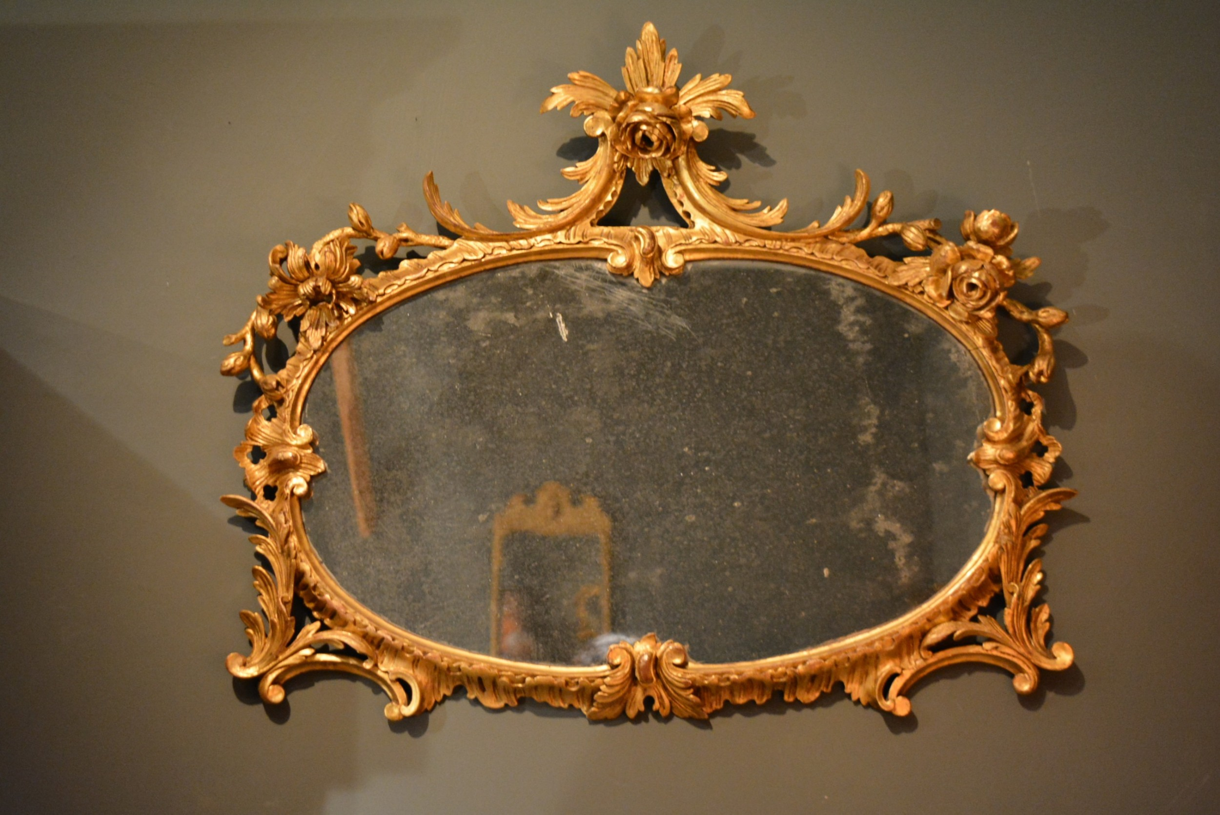 18th century carved gilt wood oval overmantle mirror