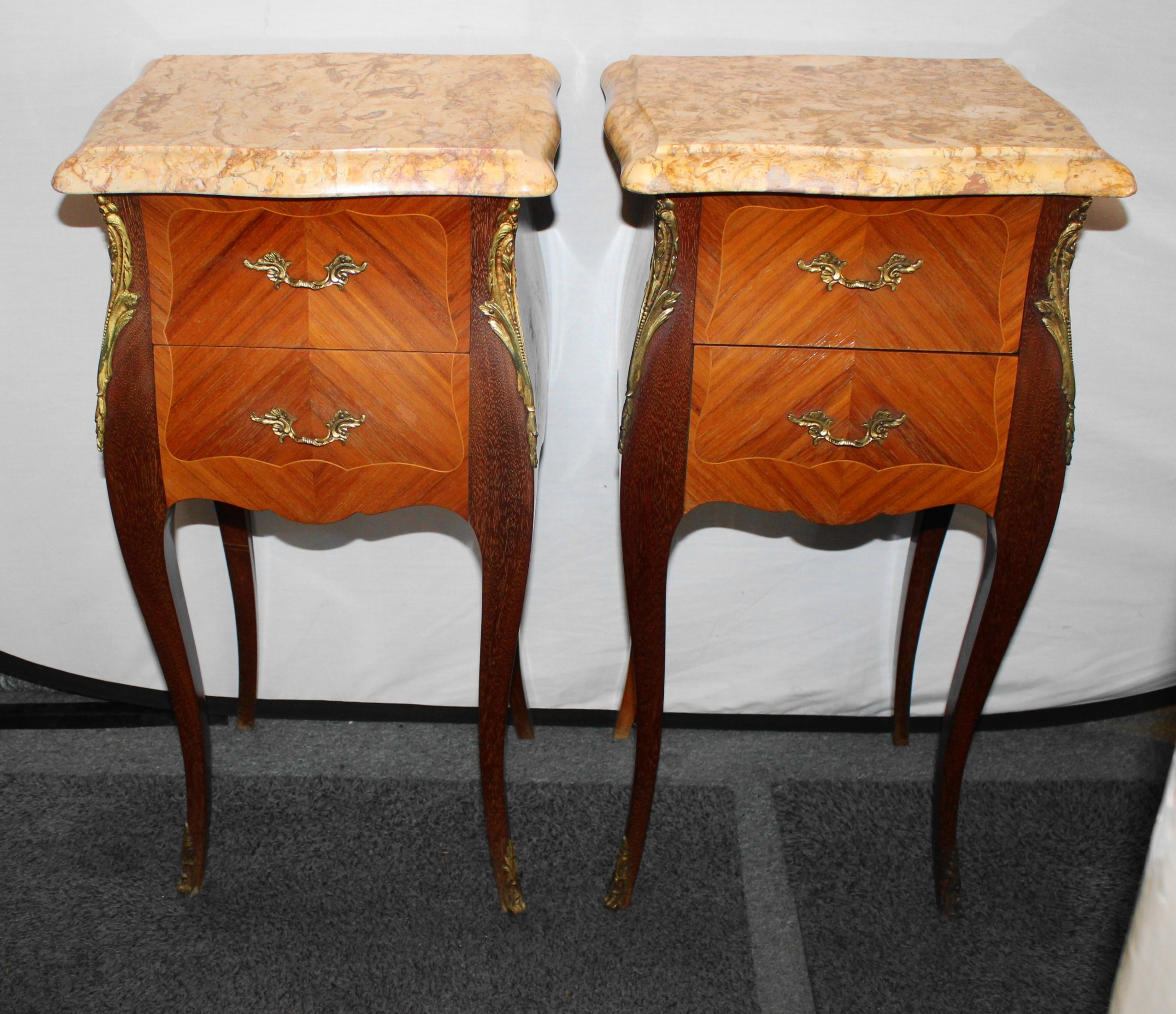 pair of kingwood bedside tables with brass mouts and pink marble tops