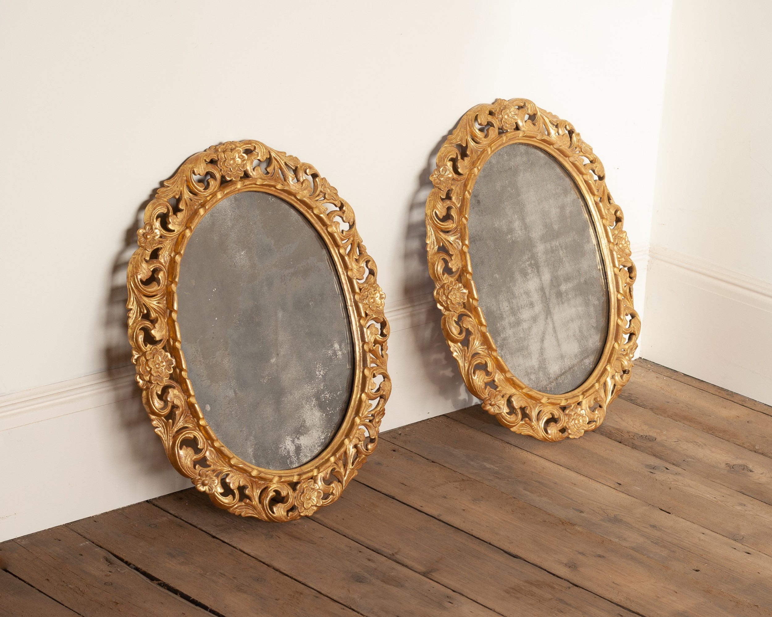 a pair of 19th century oval carved giltwood mirrors