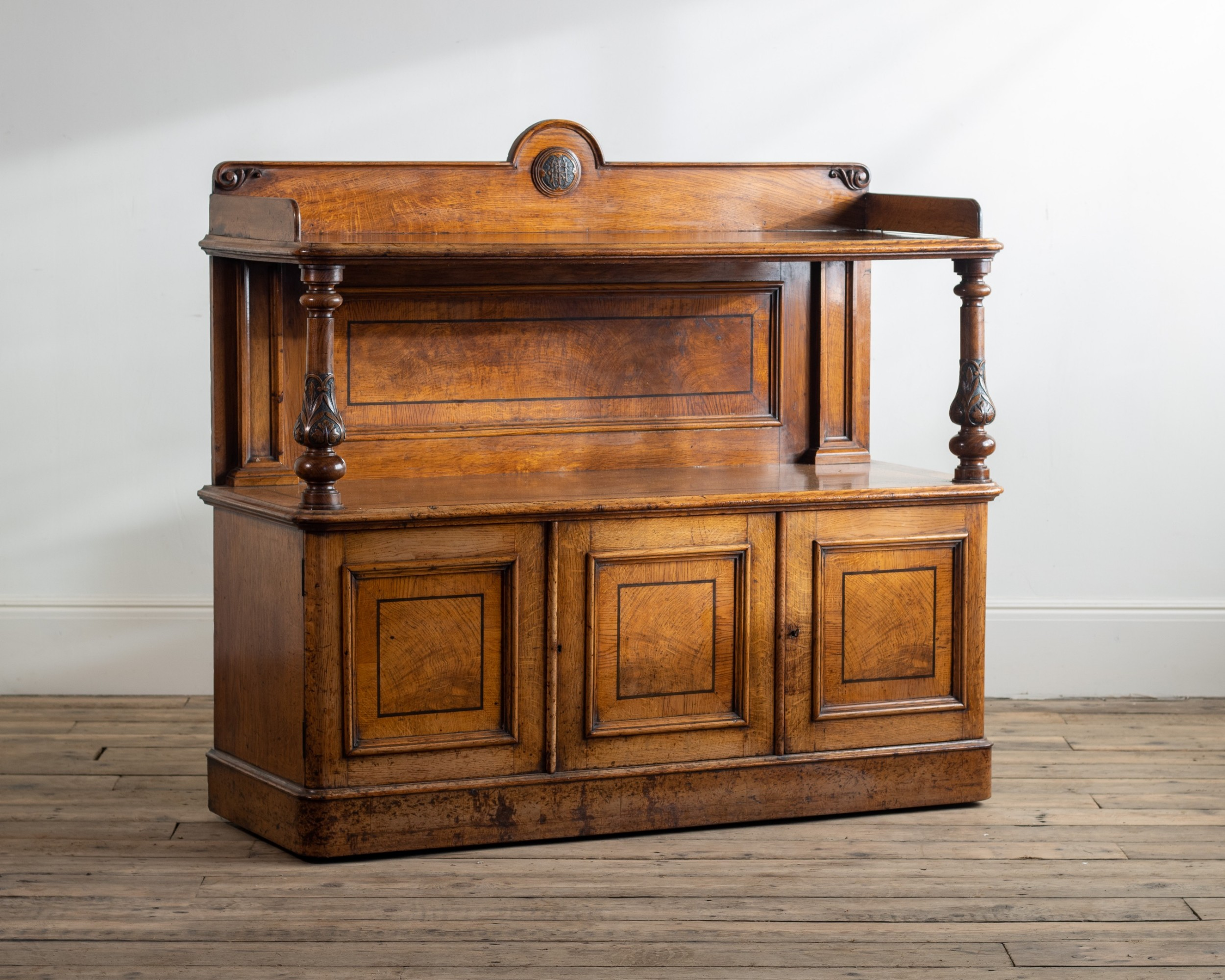 a victorian blothe rear gallery with carved monogram the base with three cupboard doorsasophisticated use of oaknde oak buffet