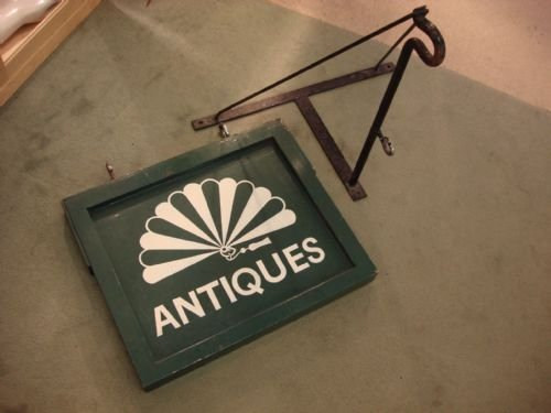 vintage early 20th century antiques shop sign with original wrought iron hanging bracket