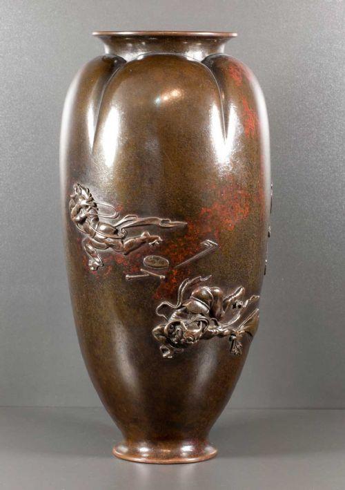 a humorous japanese meiji period bronze vase depicting shoki chasing oni's