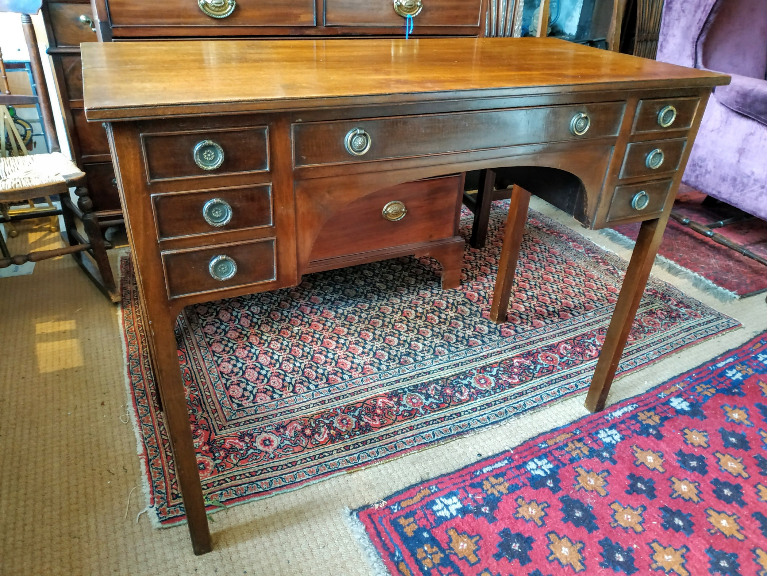 an edwardian mahogany dressing table with kneehole recess seven drawers with circular brass handles raised on moulded legs