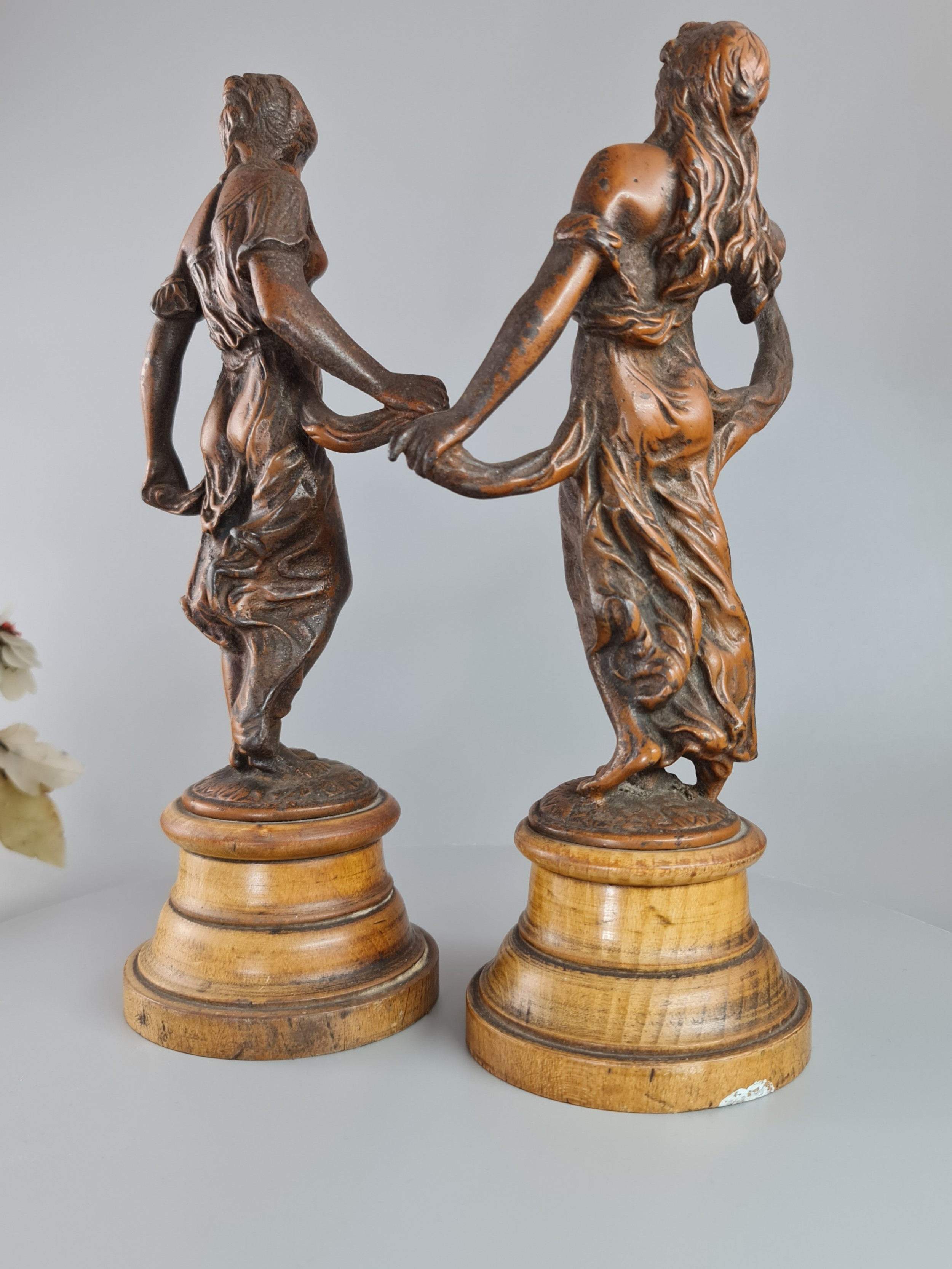 pair of neoclassical style spelter figures of 'modesty' and 'gaiety' on wooden plinths c1900