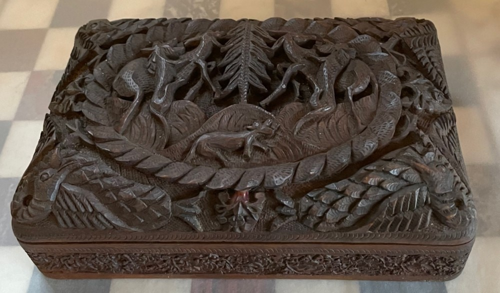 carved box depicting stylised wolves hunting deer circa 1930