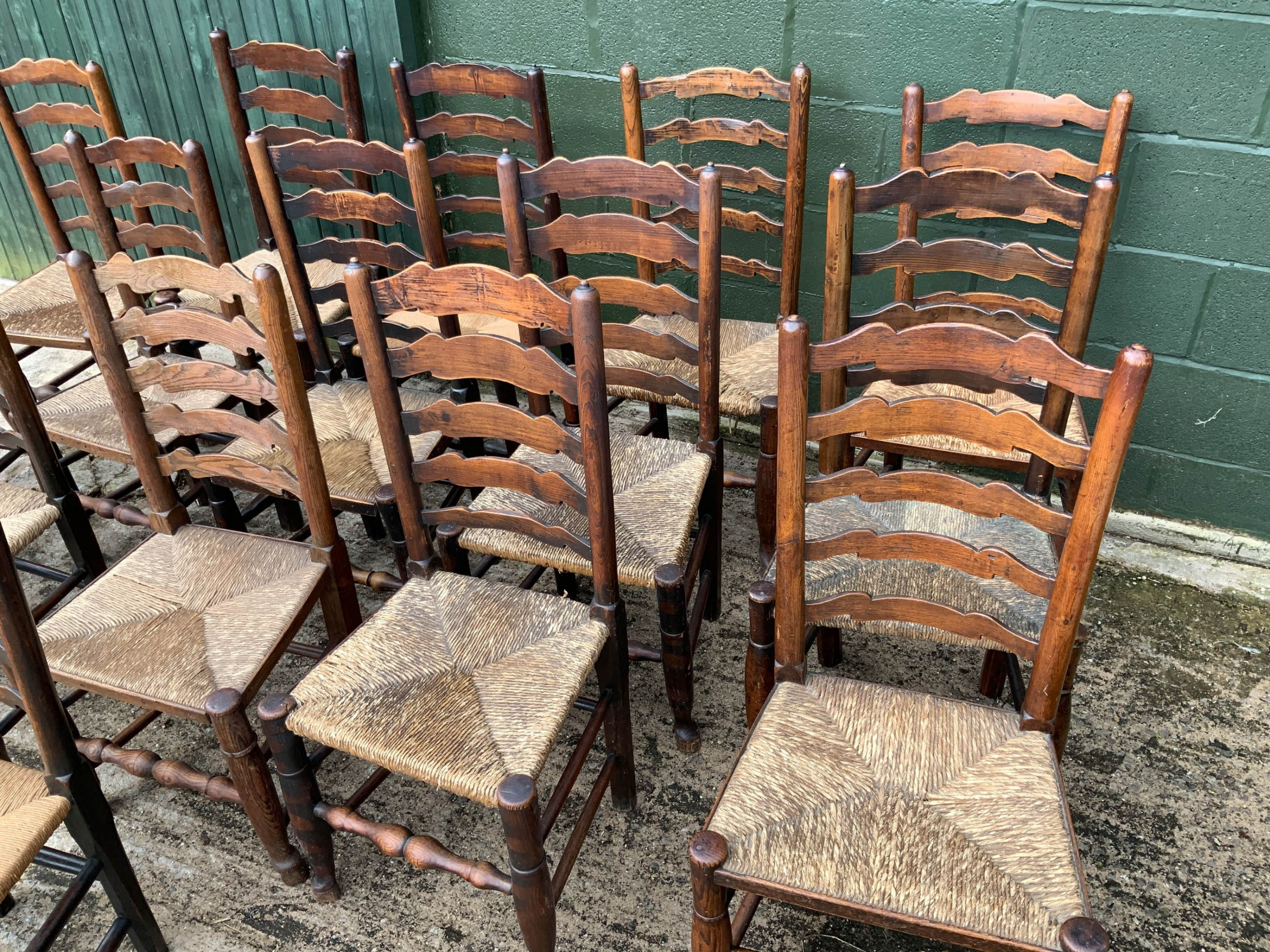 a harlequin set of 15 19th century ladder back dining chairs