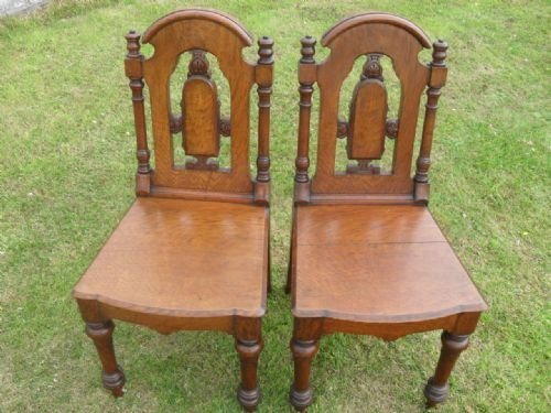pair of victorian oak hall chairs with carved turned and pierced backs