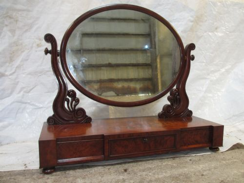 quality early victorian flame mahogany oval dressing table toilet swing mirror with three drawer base and carved shaped supports set on squashed bun feet
