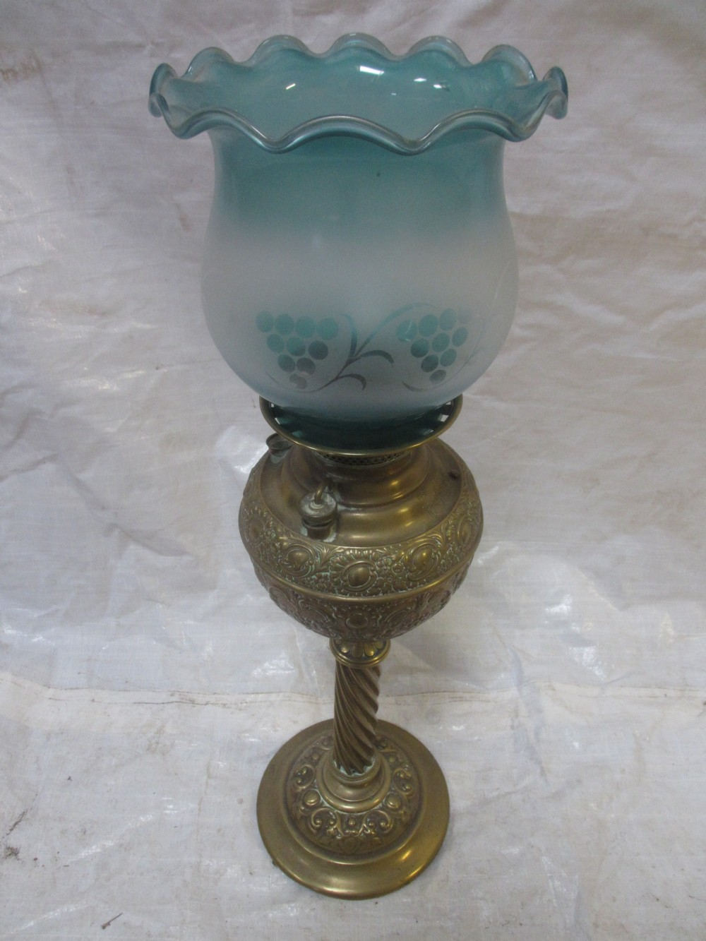 19th century brass embossed oil lamp with tinted glass shade