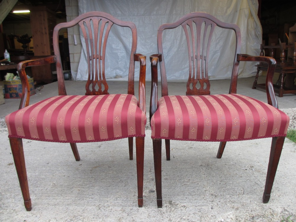 pair of georgian mahogany armchairs with shaped crest rail and pierced splat overstuffed upholstered seats on tapering forelegs