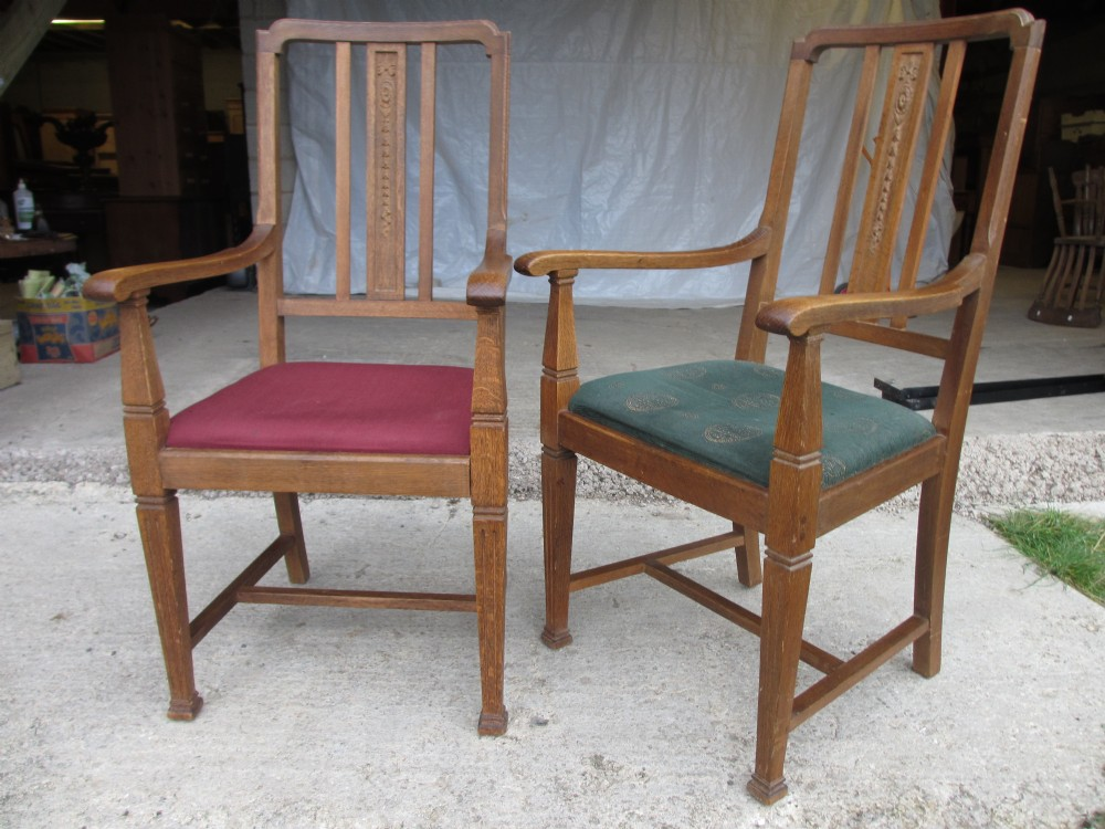 pair of edwardian oak arts crafts open carver armchairs with upholstered drop in seats carved slot back tapering and fluted supports with four stretchers