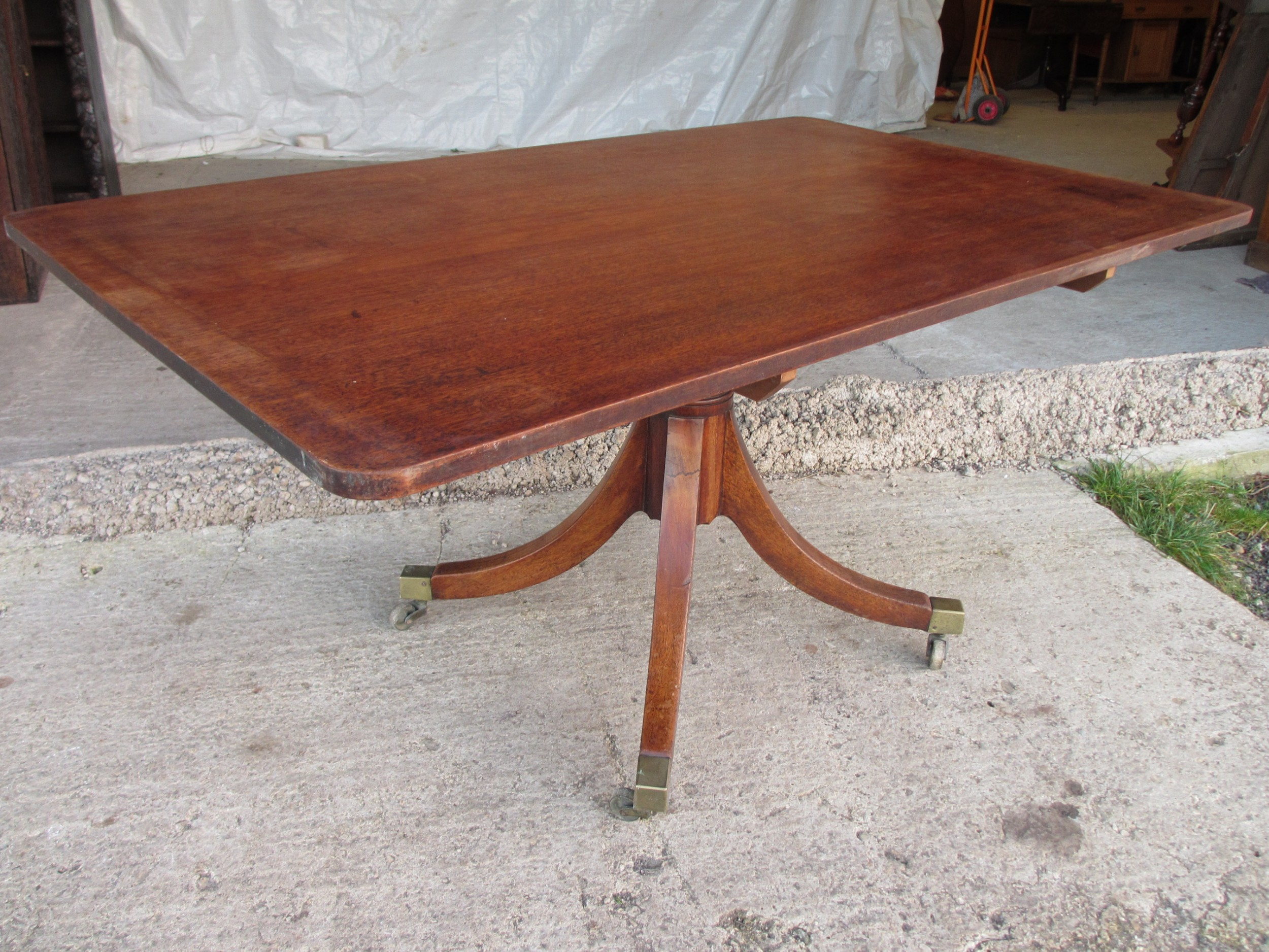 19c mahogany rectangular tilt top breakfast dining tableon turned column with splayed legs and brass castors